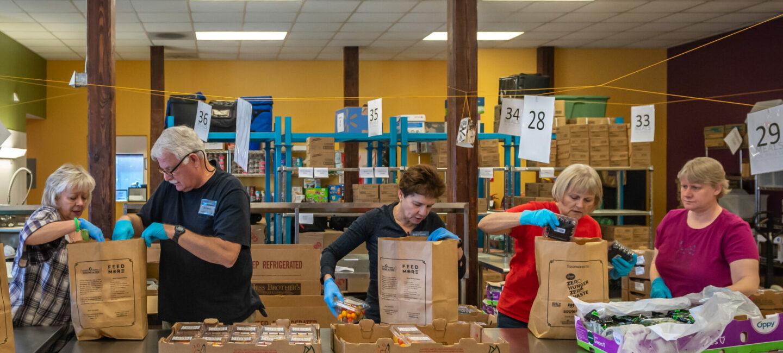 Feed More volunteers packing up bags of food_1