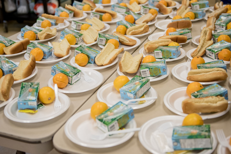 Plates with buns milk and oranges