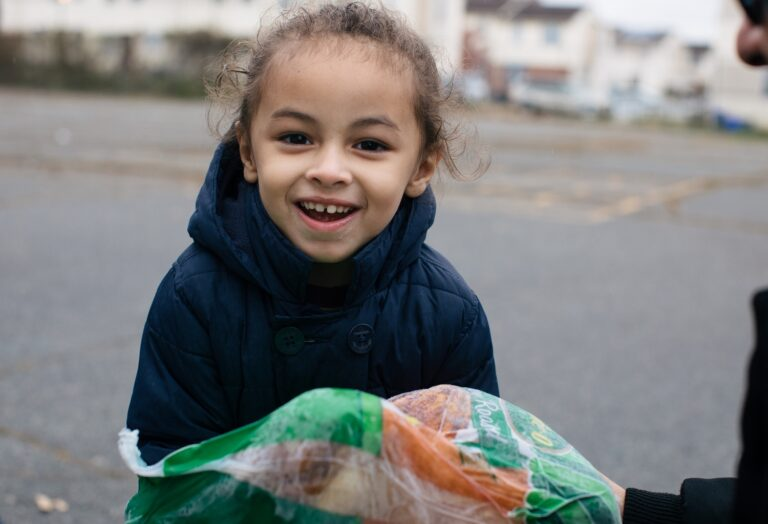Child receiving carrots at distribution