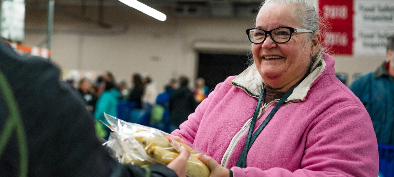 Smiling woman in pink receiving food