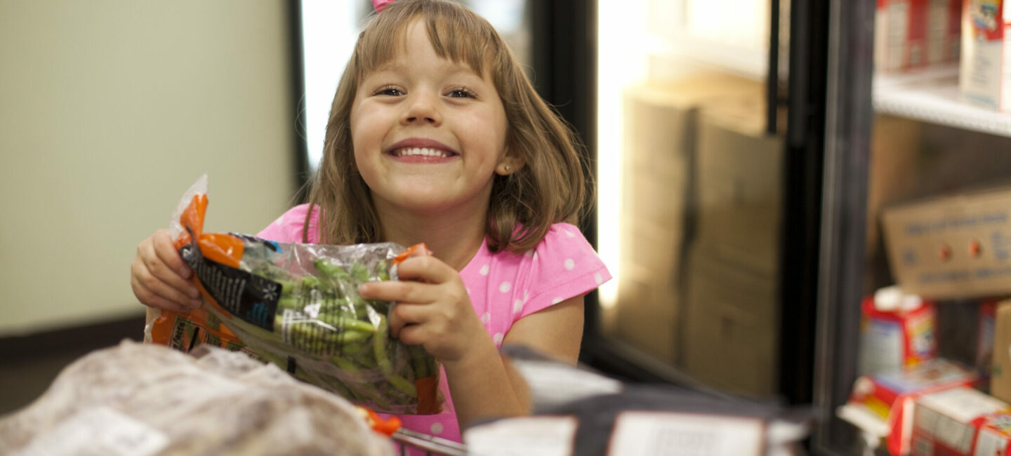 Young girl holidng bag of veggies
