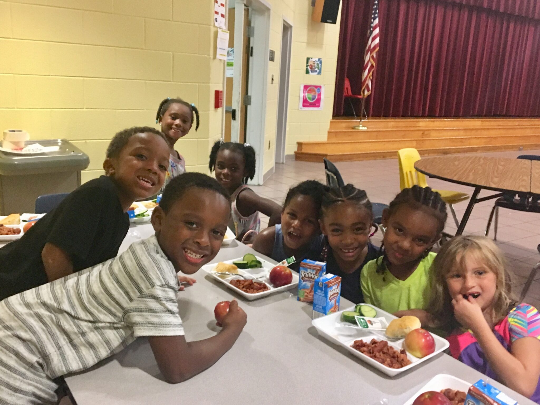 Kids smiling with food, friends and fun